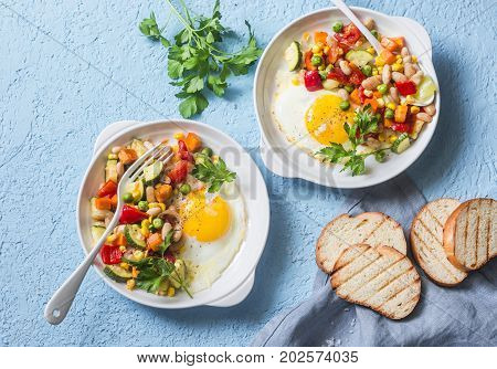 Breakfast vegetable hash with fried eggs on a blue background top view. Healthy food concept