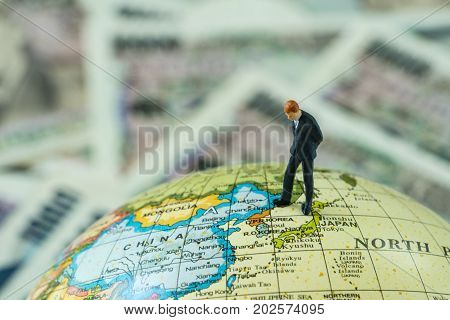 miniature figure businessman standing and looking at north korea map on globe as critical war situation concept.