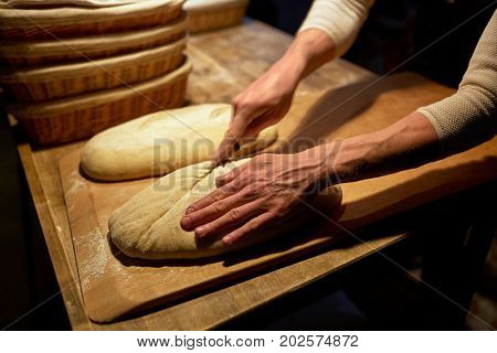 food cooking, baking and people concept - baker hands making bread and cutting dough with knife at bakery