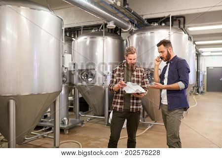 production, business and people concept - men with clipboard working at craft brewery or non-alcoholic beer plant and calling on smartphone
