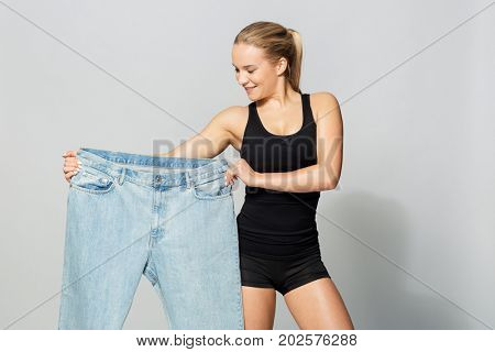 diet, weight loss and people concept - young slim sporty woman with oversize pants