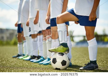 Low section portrait of junior football team : legs of boys standing in row with captain stepping on ball in foreground