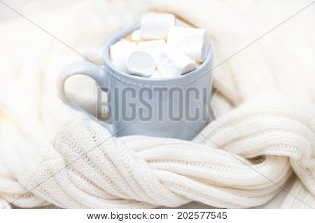 cup with hot coffee with marshmallows wrapped in knitted sweater