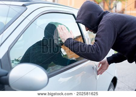Thief looking inside a car window ready to steal something