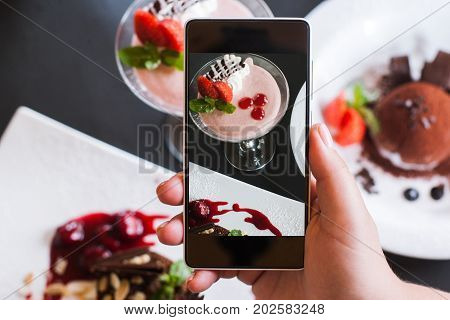 Food photography of creamy desserts by smartphone in restaurant. Delicious strawberry souffle and chocolate fondant, photoshoot and new technology, close up pov picture