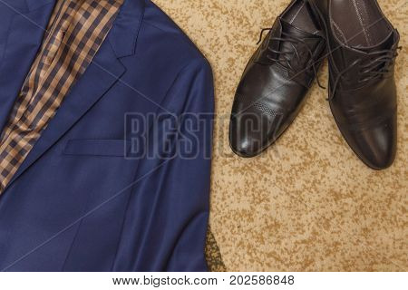 Flat lay a set of classic men's clothing such as a blue suit black shoes against the background of the carpet. View from above.