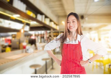 Beautiful Asian shopkeeper standing and smiling in front of her shop