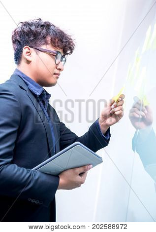 Asian Businessman working on tablet and idea