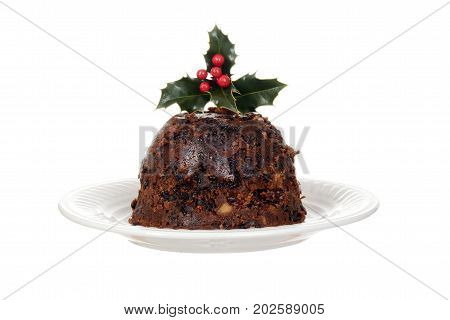 isolated christmas brandy pudding on plate with holly