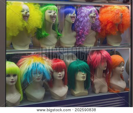 Mannequin with colorful wig and facial accessories. Sales