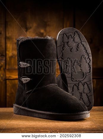 Modern winter suede boots. Pair of winter footwear, one boot standing and showing sole.