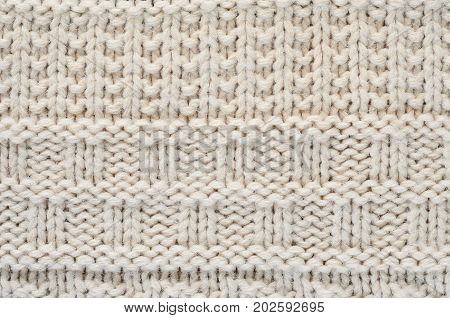 The texture of a knitted sweater is a thick beige string. Part of a sweater with various kinds of patterns close-up