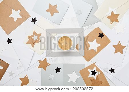 Mail correspondence background or pattern with cup of coffee and envelopes decorated stars top view. Flat lay style.
