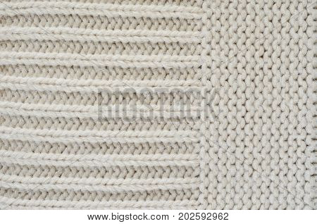 Texture of a beige knitted sweater close-up. Horizontally oriented pigtails on knitted fabric. Copy space background