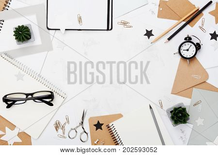 Working desk with office supply, eyeglasses, alarm clock and clean notebook top view. Flat lay. Copy space for text. Mockup frame for blogging.