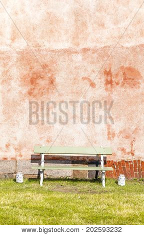 Green bench with two white large jars in front of red wall