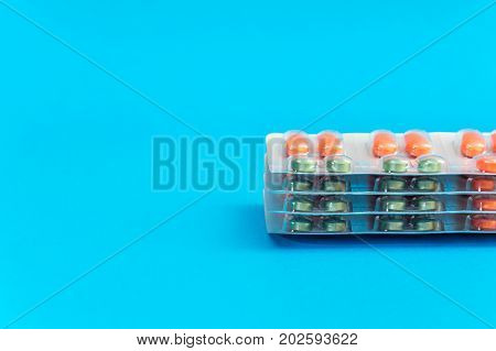 Stack of blisters with pills on the blue background.