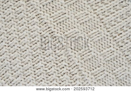 Texture of a beige knitted sweater close-up. Diagonally oriented pigtails on knitted fabric