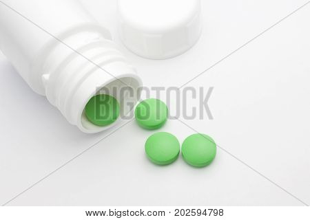 Green round pharmaceutical pills spilling out of a white pill bottle. Medical conceptual photo pharmacy theme