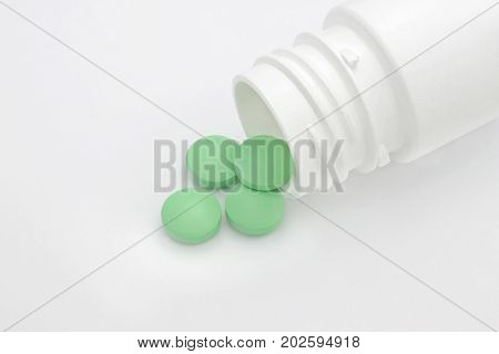Medical conceptual photo pharmacy theme. Green round pharmaceutical pills spilling out of a white pill bottle.