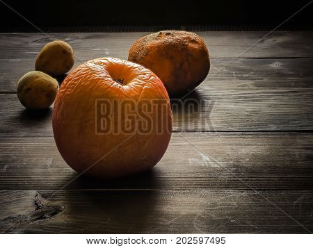 Still life with group of rotten fruits on wooden background