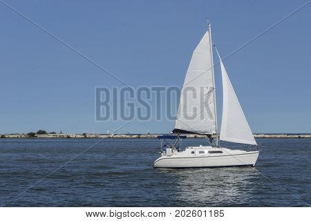 A white sailboat cruises across the harbor at Cleveland, Ohio on lake Erie