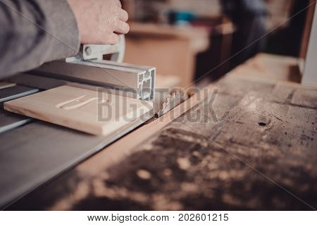 A Carpenter Works On Woodworking The Machine Tool. Saws Furniture Details With A Circular Saw