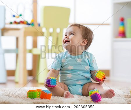 baby boy playing with toys at home nursery or kindergarten