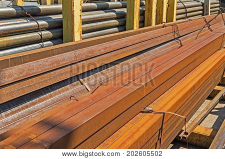 The manufactured by welding round and square rusty steel pipes piled up warehouse outdoor