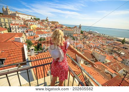 Lisbon aerial view of popular Church of Sao Vicente of Fora and Tagus river. Happy tourist woman with open arms admiring Alfama from Miradouro das Portas do Sol. Overlook of Lisbon in Portugal, Europe