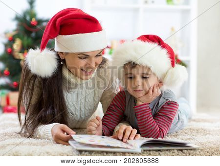 Child boy and his mother reading book at Christmas