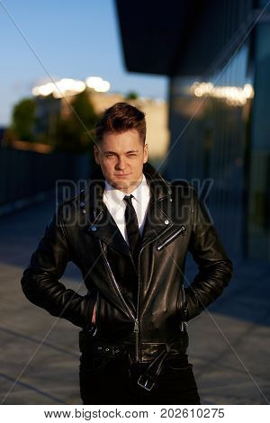 Handsome smooth-shaven young European businessman wearing jeans shirt with tie and black leather jacket posing in cityscape early in the morning having confident look keeping hands in pockets