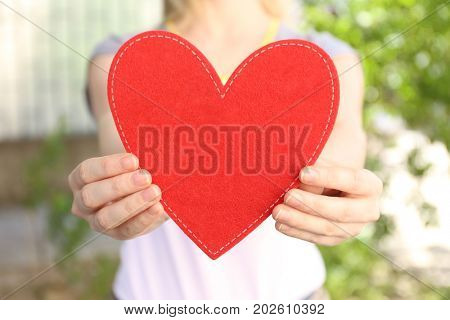 Woman holding red heart on blurred background. Volunteer concept