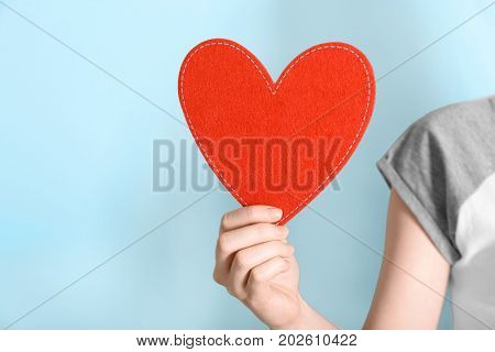 Woman holding red heart on color background. Volunteer concept