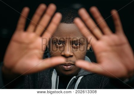 Stop gesture. Black male in selective focus. Angry African American man, facial expression, not guilty guy on dark background, emotional photo, protection concept
