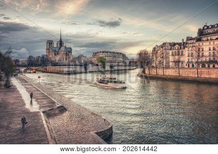 Tourist ship and Cathedrale Notre-Dame de Paris on Ile de la Cite. Paris. France