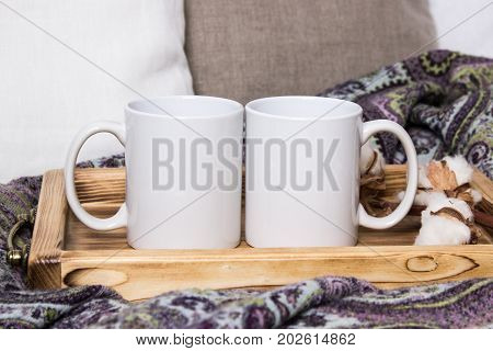 Two white mugs, pair of cups on a wooden tray, the Mockup. Cozy home, wooden background, cotton and wool decorations, winter gifts.