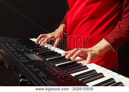 Pianist play the keys of the electronic synthesizer on a black background