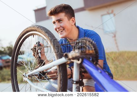Teenager boy repair tire on bicycle summer outdoor photo