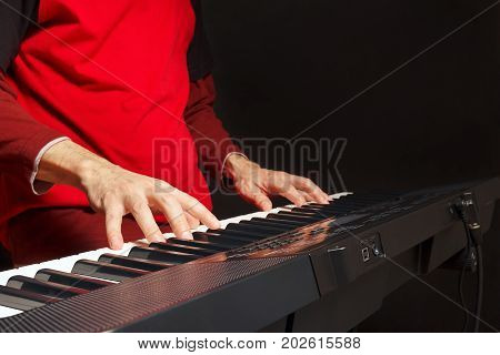 Pianist play the keys of the electronic piano on a black background