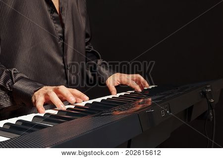 Pianist play the keys of the piano on a black background