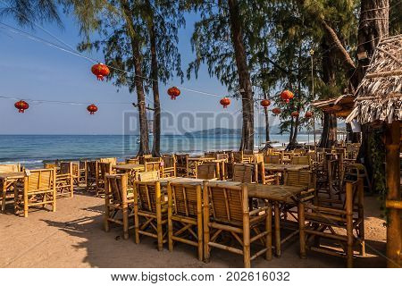 Restaurant on Bang Tao beach Phuket Thailand early in the morning. Bang Tao Bay in the background