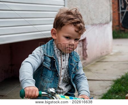 European curly-haired boy in a denim jacket driving a bike near the house