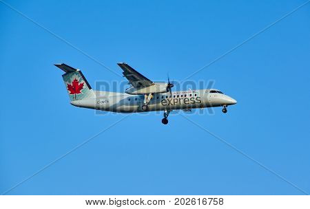 MONTREAL CANADA - AUGUST 28 2017 : C-GMTA - Bombardier Dash 8 Q300 landing plane. Air Canada Express is a brand name under which four regional airlines operate feeder flights for Air Canada.