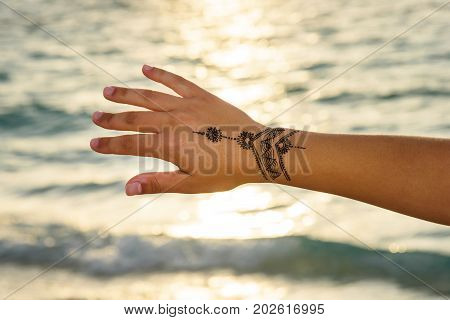 henna tattoo painting on the hand at sunset