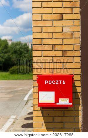 Red Poczta Polska mail box on a brick wall on August 2017 in Poznan Poland