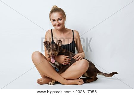 Studio Shot Of Beautiful Girl Sitting Crossed Legs With Her Dog, Having Happy Expression While Spend