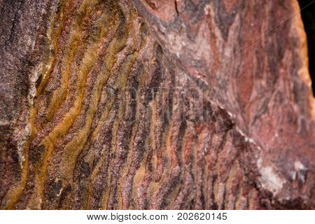 An interesting, unusual and beautiful texture of rock in waves of red shade