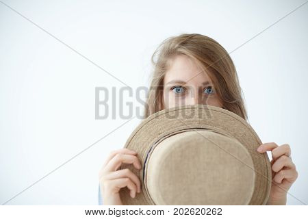 Close up horizontal studio portrait of beautiful mysterious girl with blue eyes and fair hair looking at camera peeping out from behind her summer round hat having playful and enigmatic look