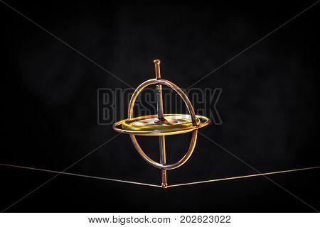 Toy gyroscope balancing on a line against a dark background